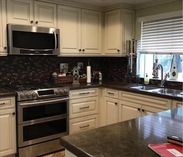 Kitchen with dark countertops and back splash and white cabinets