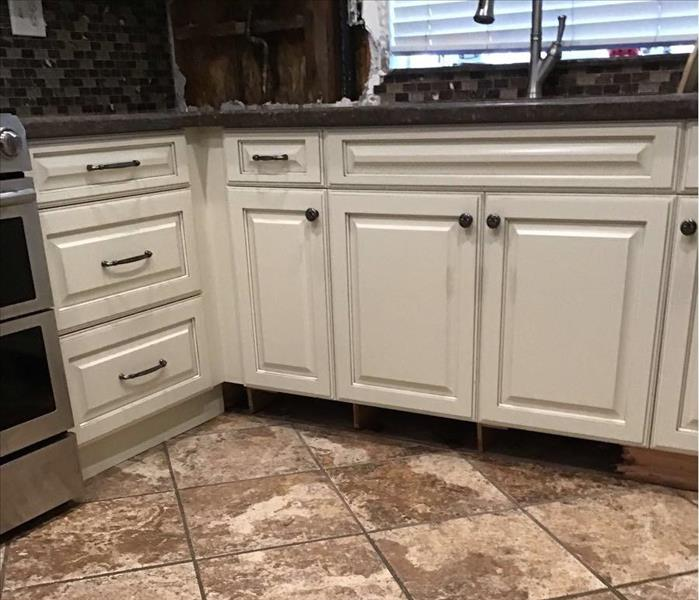 Kitchen cabinets and floor with removed toe kicks and backsplash next to sink.