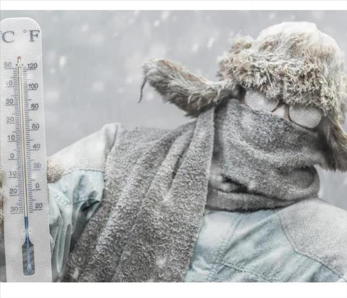 A person in glasses and a grey parka holds a thermometer up in front of them during a snowstorm.