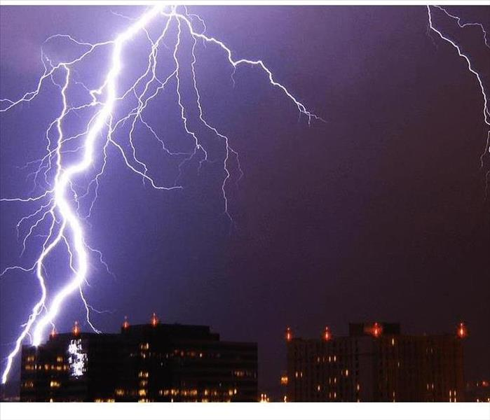 A white lightning bolt cuts through the night sky above a metropolitan cityscape.