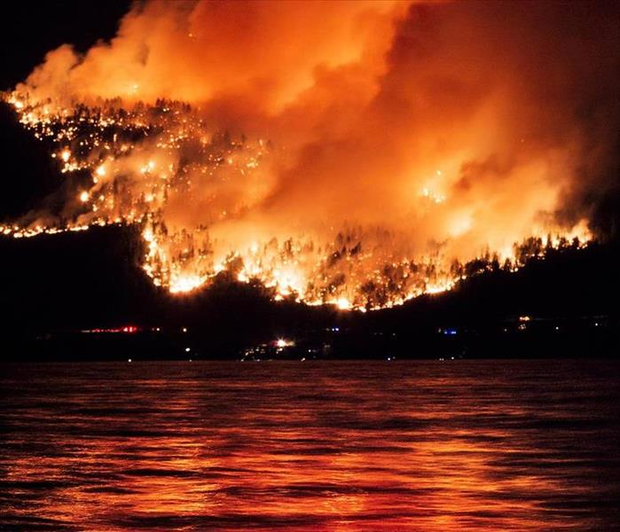 A large wildfire burns a mountainside at night. A large body of water can be seen in the foreground