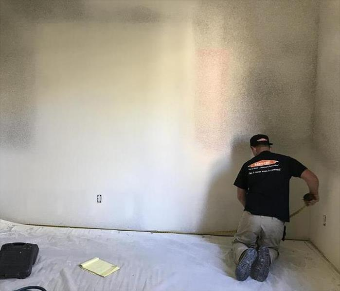 A white room with a SERVPRO employee in a black shirt measuring the wall while sitting on the ground.